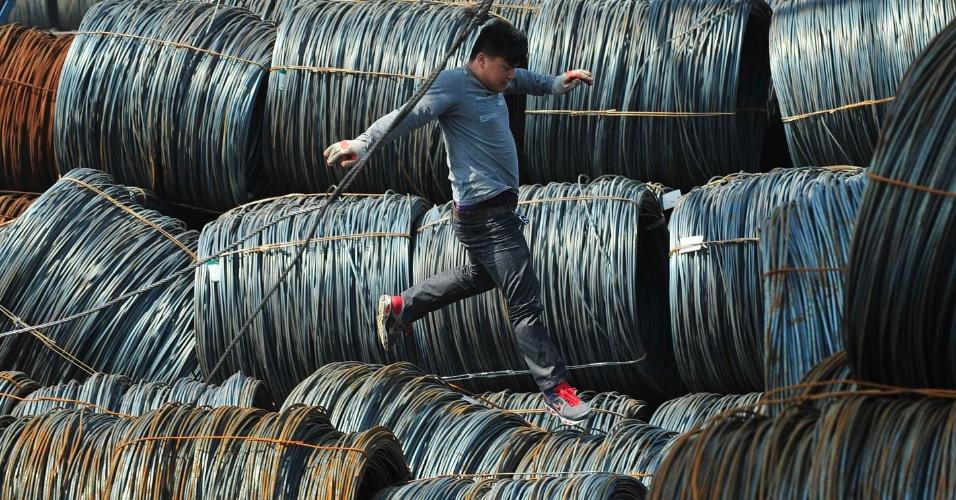 Trabalhador caminha sobre bobinas de aço em mercado de Shenyang, na China