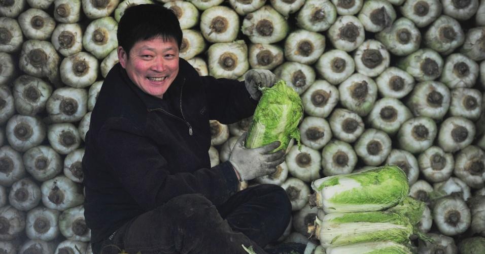 Vendedor espera por clientes em frente a pilhas de acelgas chinesas em mercado de Shenyang, na China