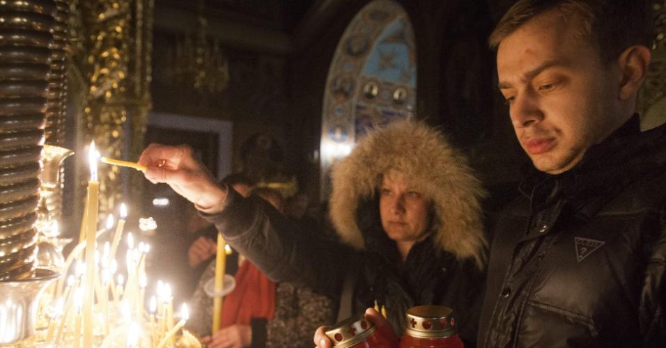 Crentes ortodoxos acendem velas em frente à catedral Nasterea Domnului, em Chisinau, na Moldávia. Os ortodoxos celebram a Páscoa segundo o calendário Juliano
