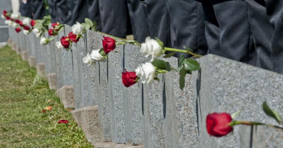Flores são colocadas sobre as lápides das vítimas do Titanic enterradas no cemitério Fairview Lawn, em Halifax (Canadá)