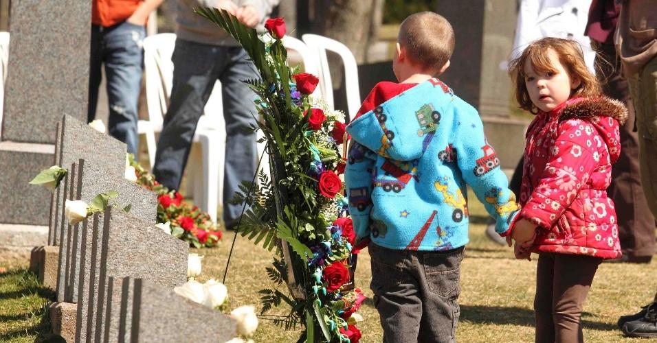 Menino e menina participam de memorial das vítimas do Titanic enterradas no cemitério de Fairview Lawn, em Halifax (Canadá). No cemitério, há 121 pessoas enterradas que tripulavam o navio