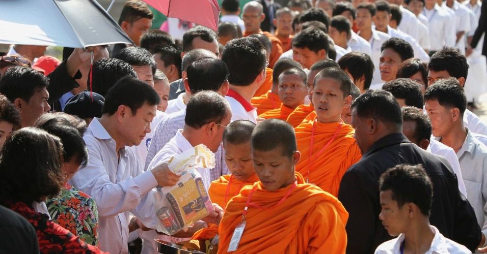 O ex-primeiro-ministro tailandês, Thaksin Shinawatra (à esquerda), oferece comida aos monges budistas durante celebração do Ano Novo tailandês, no templo de Angkor, na província de Siem Reap, no Camboja, neste domingo (15)