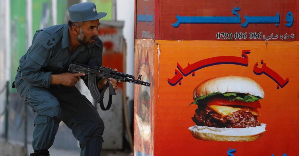 Policial afegão se posiciona perto de local de ataque em Cabul neste domingo (15). Uma casa ocupada por diplomatas britânicos no centro da cidade foi alvo de ataques