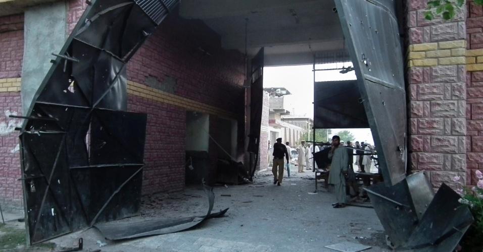 Policial e autoridades de segurança observam portão destruído após fuga de presos em Bannu, no noroeste do Paquistão, neste domingo (15). Militantes islâmicos invadiram a prisão durante a noite e libertaram cerca de 400 detentos, incluindo um condenado à pena de morte por tentar assassinar o ex-presidente Pervez Musharraf, segundo autoridades