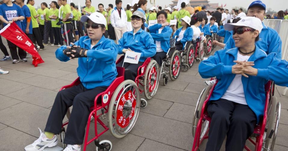 Portadores de necessidades especiais aquecem antes do início de corrida que marca a abertura do Festival Internacional de Atletismo na Praça Tiananmen, em Pequim, na China. Segundo organizadores, cerca de 20 mil participam do evento