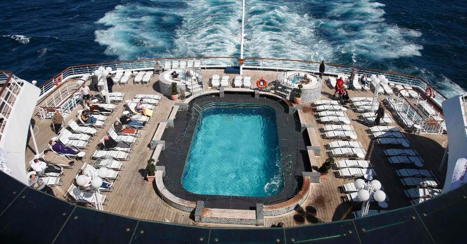 Tripulantes do cruzeiro em homenagem ao Titanic aproveitam dia de sol no deck do navio. O cruzeiro saiu de Southampton (Reino Unido) e está fazendo a mesma rota do navio que naufragou há 100 anos