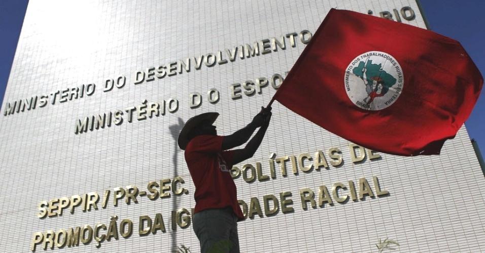 Integrante do MST agita bandeira em frente ao prédio do Ministério do Desenvolvimento Agrário, em Brasília. O movimento realiza uma série de ocupações e protestos pelo país nesta segunda-feira (16). A principal manifestação acontece em Brasília, onde cerca de 1,5 mil sem-terra ocuparam, nesta manhã, o prédio do ministério. O alvo principal dos protestos é a presidente Dilma Rpusseff, que teria reduzido o ritmo de criação de assentamentos e cortado crédito para área