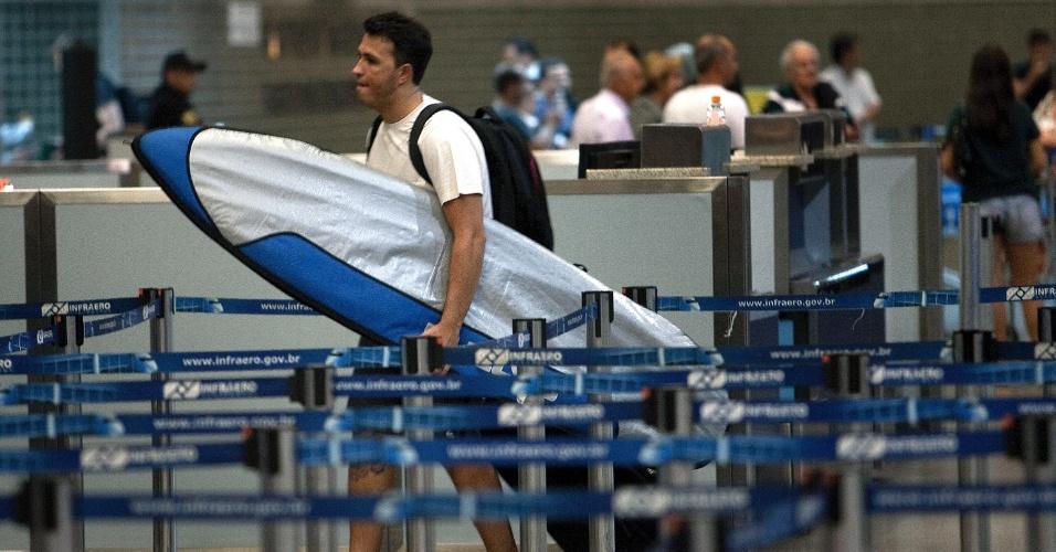 Jovem com prancha de surf caminha em direção ao balcão da companhia aérea, no aeroporto de Cumbica, em Guarulhos (SP)