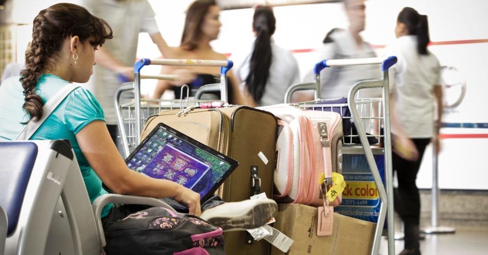 Passageira usa computador no aeroporto de Cumbica, em São Paulo