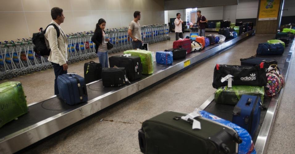 Passageiros aguardam para pegar suas bagagens em uma das esteiras do desembarque internacional no aeroporto de Cumbica, em São Paulo