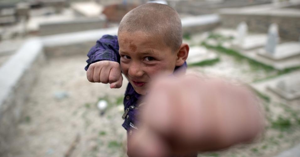 Garoto imita boxeador em cemitério em Cabul, no Afeganistão