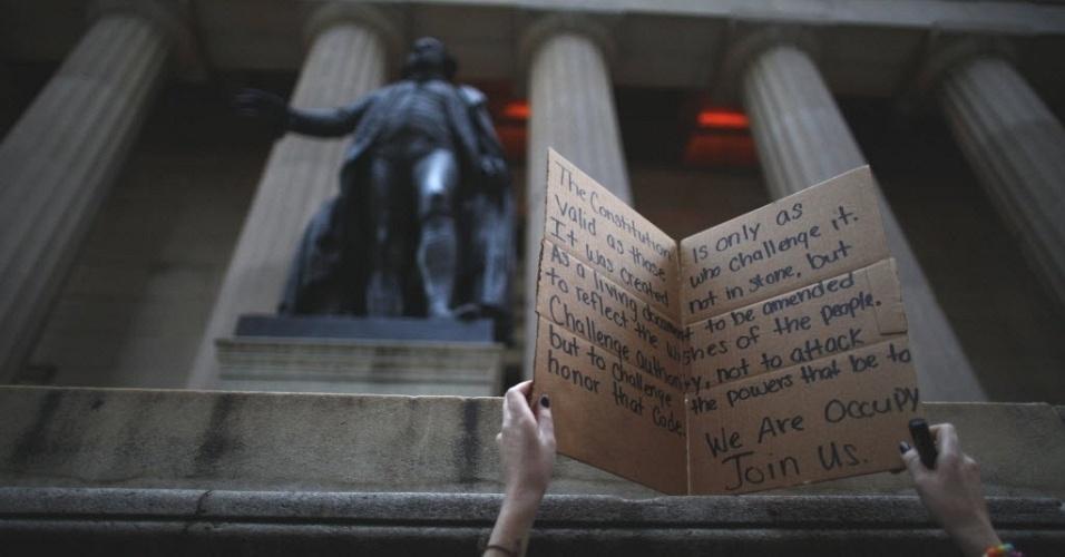 Manifestante do movimento Occupy Wall Street ajeita cartaz em frente à estátua de George Washington, primeiro presidente dos EUA