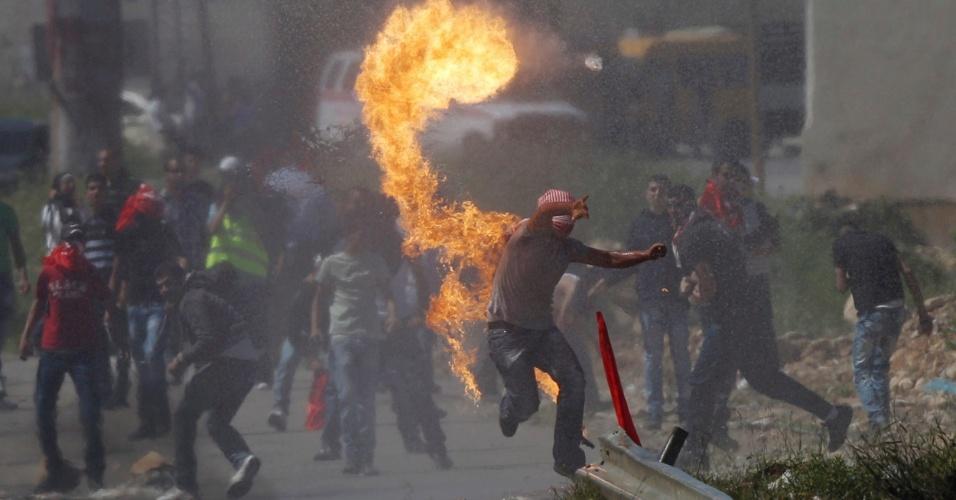 Manifestantes palestinos lançam coquetéis Molotov contra soldados palestinos em Ramallah, na Cisjordânia, próximo à prisão israelense de Ofer