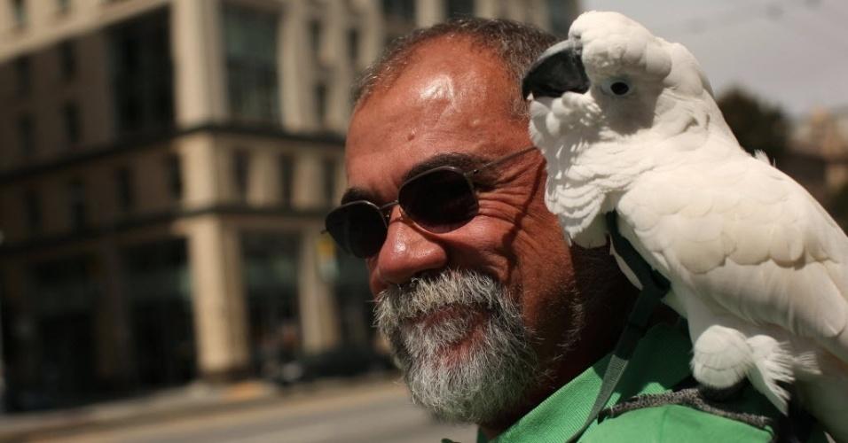 Paul Tortora e sua ave calcatua aguardam por ônibus em São Francisco, na Califórnia (EUA)