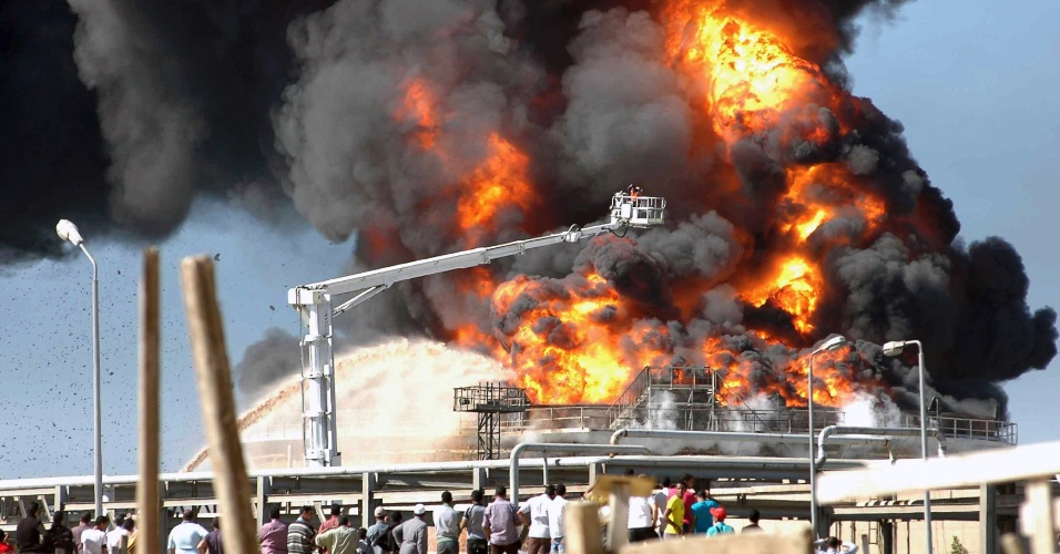 Pessoas observam a tentativa de bombeiros de conter as chamas após fortes explosões em refinaria da Nasr Petroleum Company em Suez, no Egito