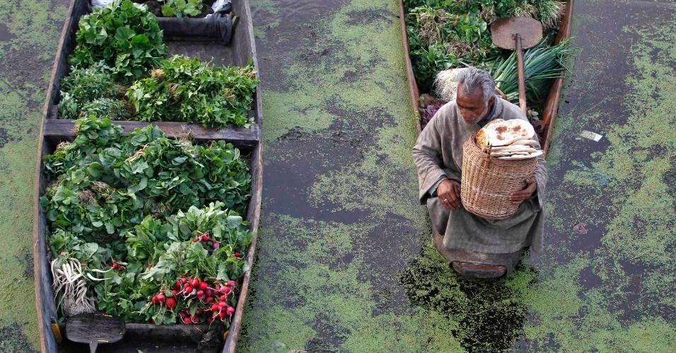 Vendedor de verduras segura cesta de pães em mercado flutuante no lago Dal, em Srinagar, na Caxemira