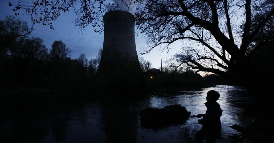 Garoto pesca peixes no rio Aare,  perto da usina nuclear Goesgen, na cidade suíça de Niedergoesgen