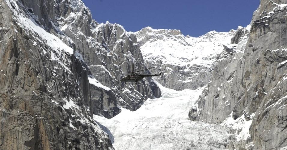Helicóptero do Exército do Paquistão (topo, ao centro) com o presidente Asif Ali Zardari e autoridades militares sobrevoa local de avalanche próximo à geleira Siachen, próximo à fronteira do país com a Índia. As equipes de resgate buscam 140 soldados que estavam no local na hora do deslizamento