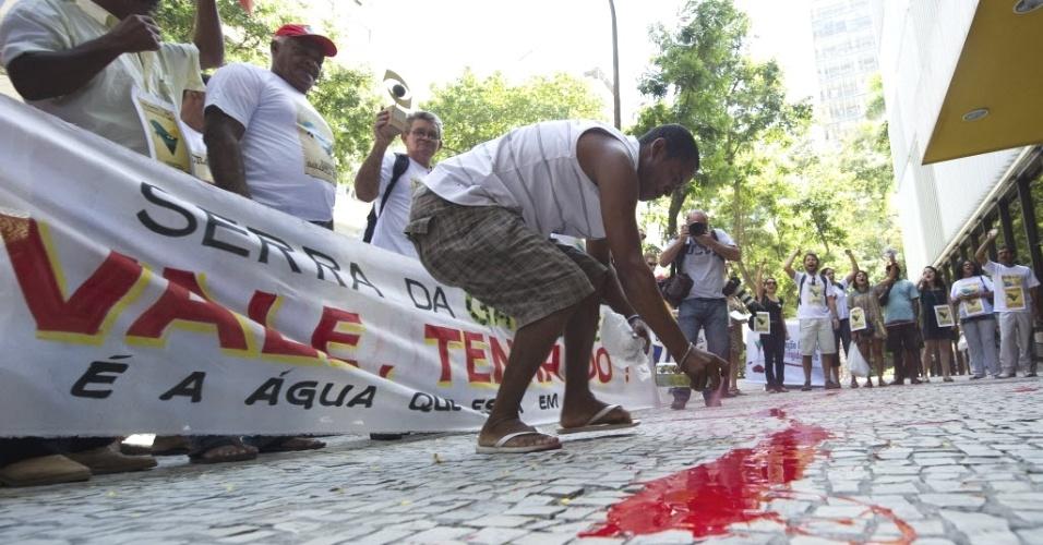 Manifestante pinta calçada de vermelho durante protesto em frente à sede da empresa Vale do Rio Doce no Rio de Janeiro. A manifestação é contra as obras da usina de Belo Monte, que prevê a construção de uma hidrelétrica no rio Xingu