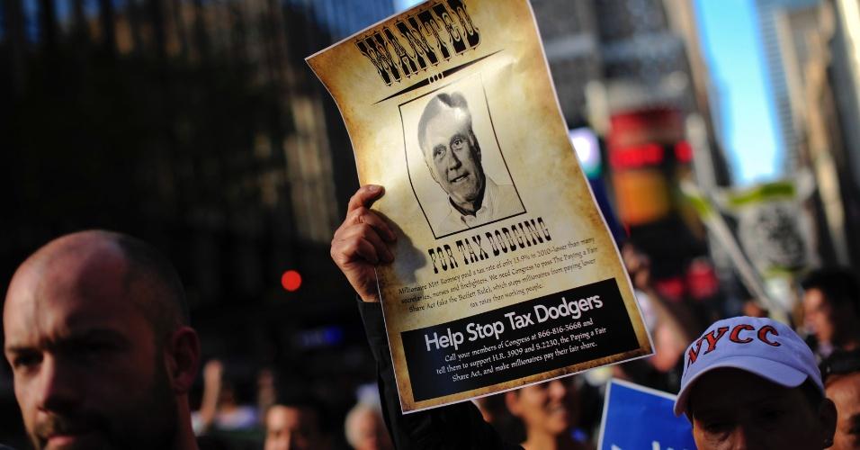 Manifestante segura foto do candidato à presidência dos Estados Unidos Mitt Romney em Nova York durante protesto contra o código fiscal que permite que bancos e empresas paguem imposto menor