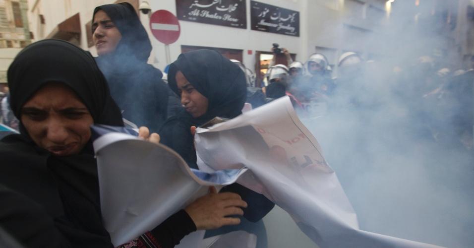 Manifestantes tentam se proteger após a explosão de uma granada de som lançada pela polícia durante protesto em Manama, no Bahrein, pela libertação do ativista de direitos humanos Abdulhadi al-Khawaja