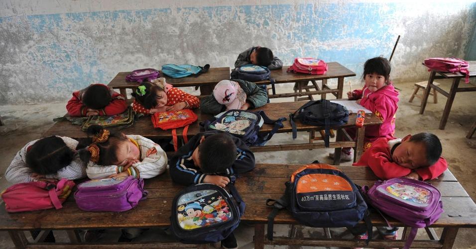 Menina observa colegas dormindo sobre as carteiras em escola primária no condado de Yuexi, na China