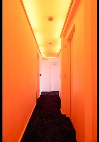 Corredor do andar laranja do hotel Pantone, em Bruxelas -- tanto os quartos quanto andares têm um cor dominante específica. O projeto é assinado pelo arquiteto Olivier Hannaert e pelo designer de interiores Michel Penneman