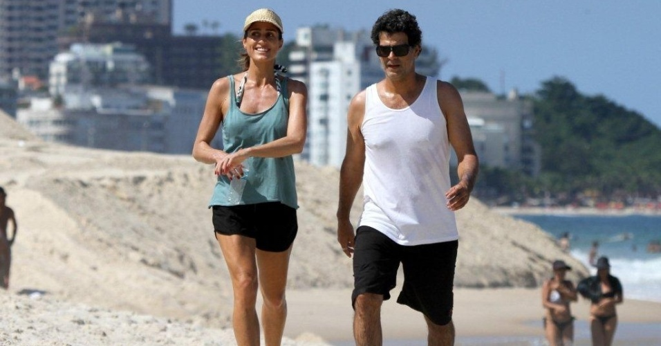 Cynthia Howlett e Eduardo Moscovis caminham pela areia da praia de Ipanema, zona sul do Rio (20/4/2012)