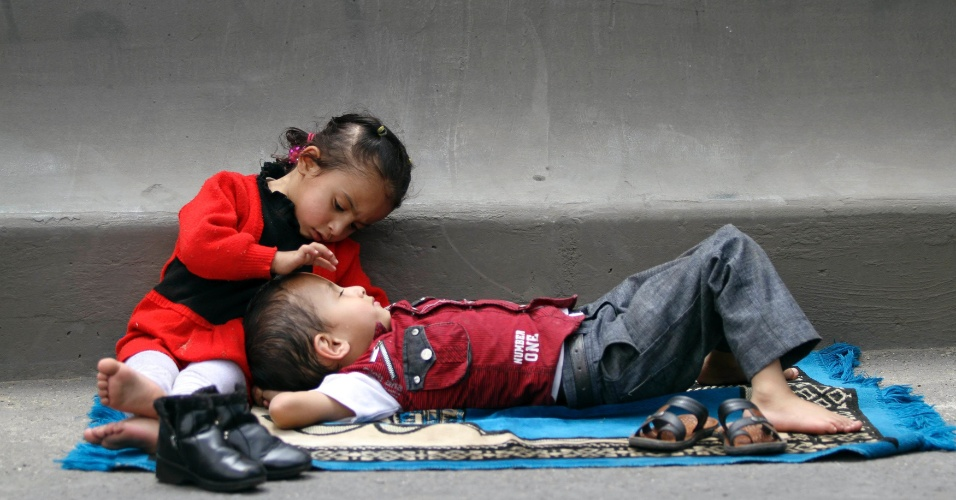 Menina se debruça sobre um menino durante as orações semanais de sexta-feira em um comício em Sanaa