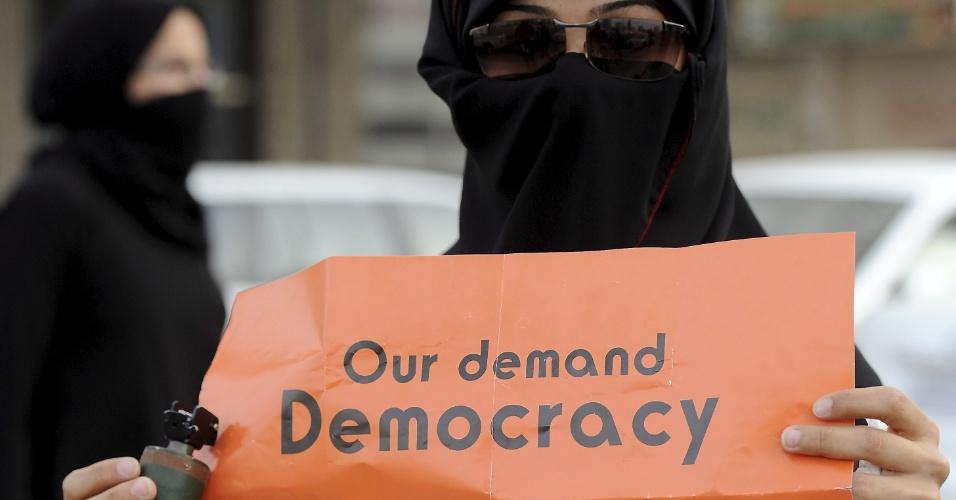 Mulher com bomba de gás lacrimogênio em uma das mãos segura cartaz com pedido de democracia no Bahrein, em Manama, capital do país