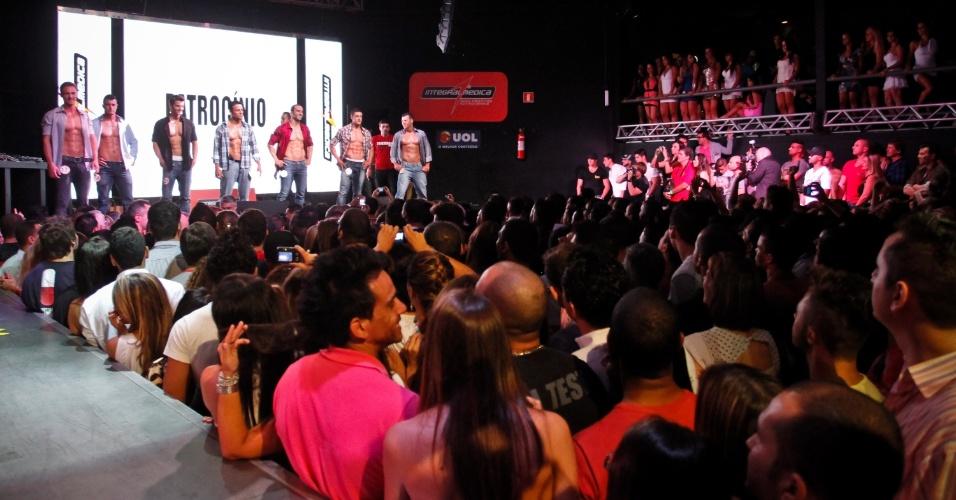 Plateia acompanha desfile de homens com calça e camisa