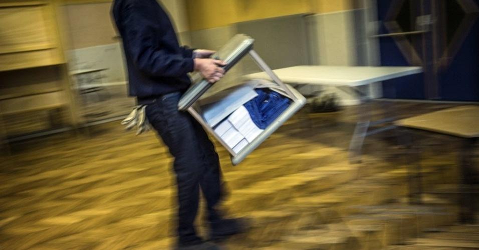 Fiscal eleitoral carrega urna em Lyon, na França, que realiza eleições presidenciais no domingo (22)