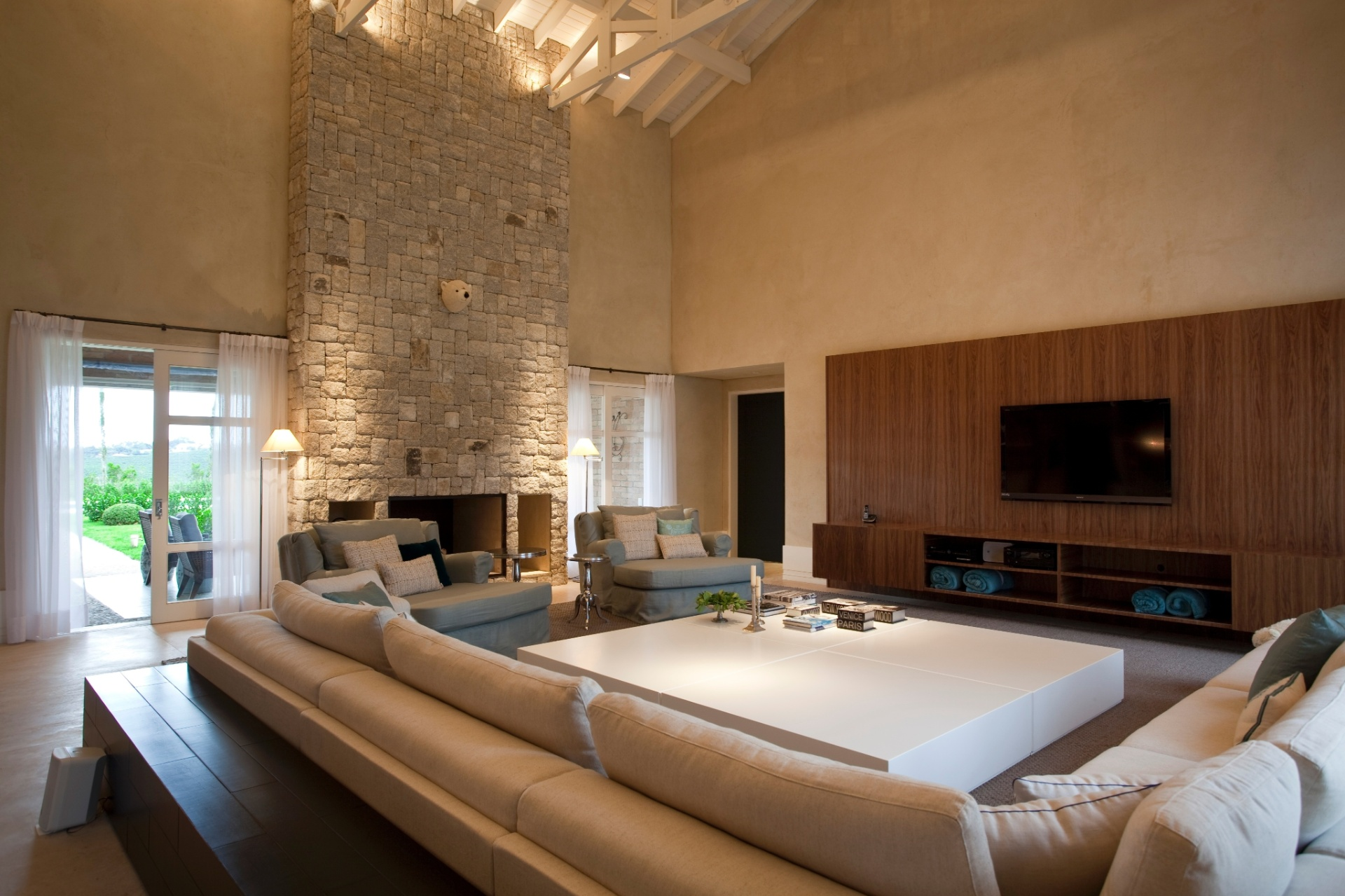 A lareira foi projetada pelo arquiteto e tem face dupla, para a sala de TV e para o estar da varanda; o telhado, com imensas tesouras aparentes, é proposital e dá uma cara moderna aos ambientes. O projeto a casa no interior de SP é de Maurício Karam