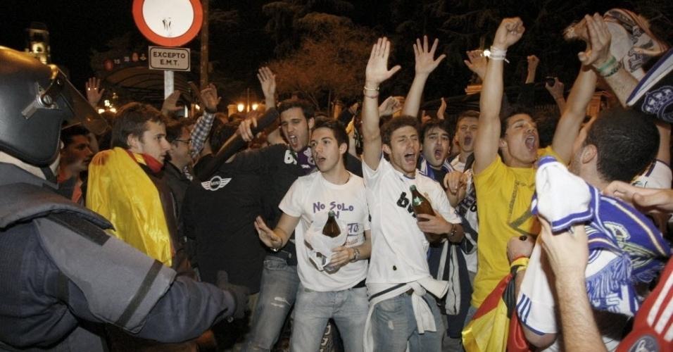 Torcedor do Real Madrid pede calma à policial durante as celcebração da vitória sobre o Barcelona