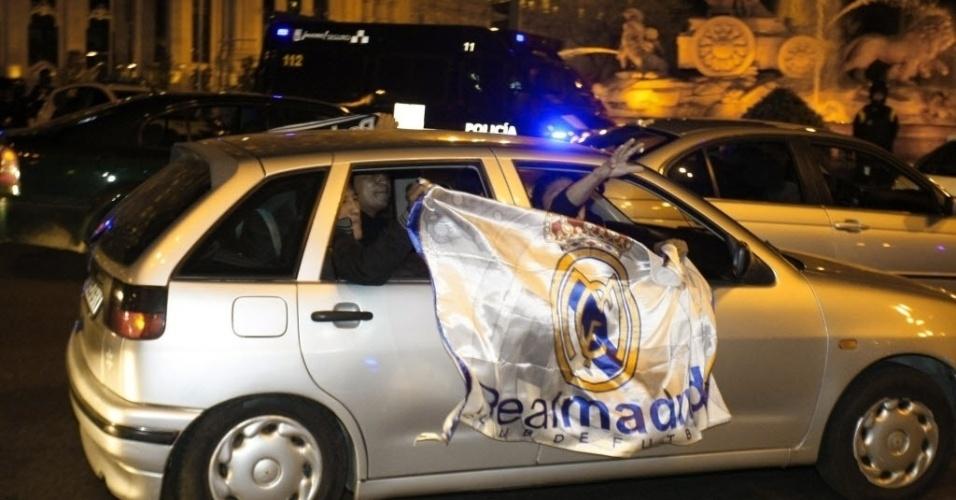 Torcedores merengues estendem a bandeira do Real Madrid no carro