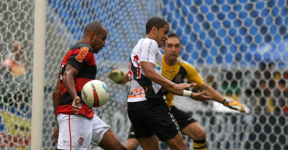 Atacante do Flamengo, Deivid tenta levar a bola com a mão marcado por Rômulo, do Vasco