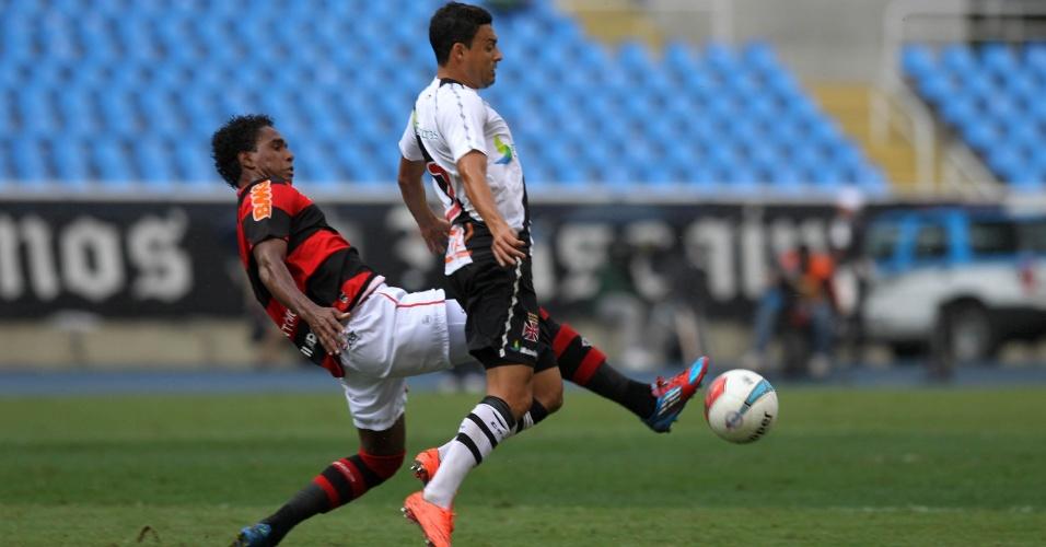 Luiz Antônio, do Flamengo, tenta um carrinho para desarmar o atacante Éder Luis, do Vasco