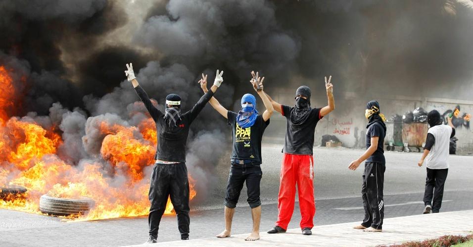Manifestantes fazem o símbolo da vitória após queimarem pneus em Budaiya, a oeste de Manana