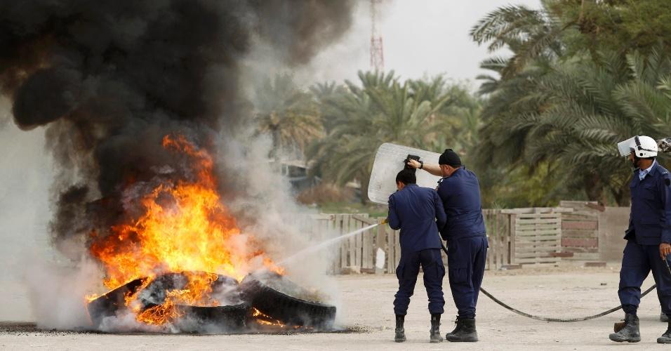 Policiais tentam apagar fogo de barricada em Manama