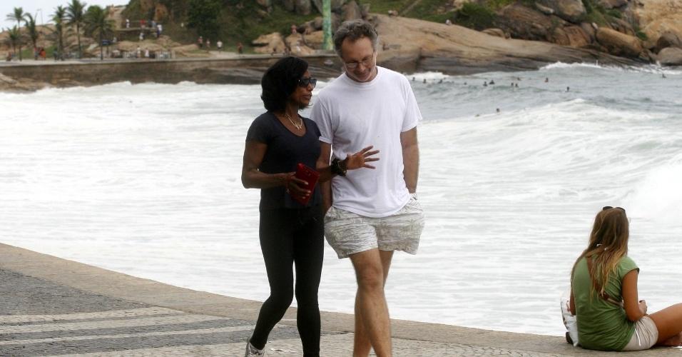A jornalista Glória Maria caminha acompanhada de um amigo pela orla da praia do Arpoador, zona sul do Rio (23/4/12)