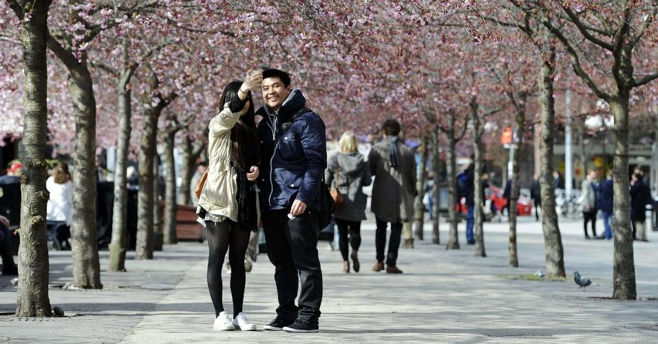 Casal se fotografa com flores de cerejeiras ao fundo em Estocolmo, na Suécia