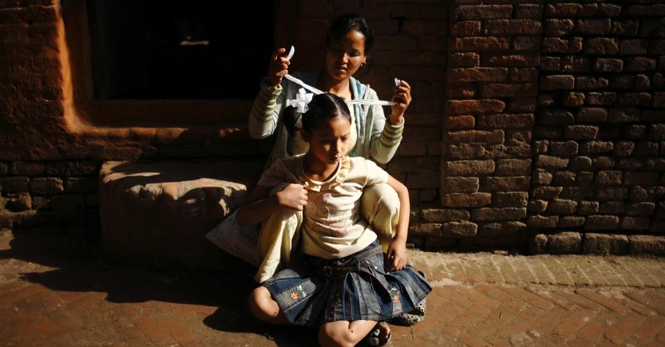 Menina arruma cabelo antes de ir para a escola em Bhanktapur, no Nepal