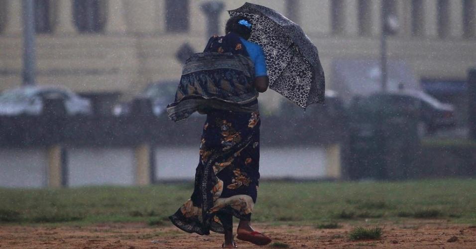 Mulher caminha em meio à chuva de monção com ventos fortes em Colombo, capital do Sri Lanka