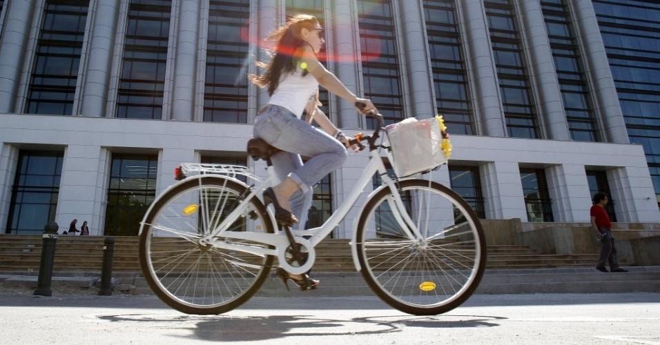 Mulher passa de bicicleta diante do prédio da Biblioteca Nacional da Romênia, reaberta nesta segunda-feira (23). Instalada em um prédio da era comunista reformado, o lugar tem um acervo de mais de 12 milhões de livros
