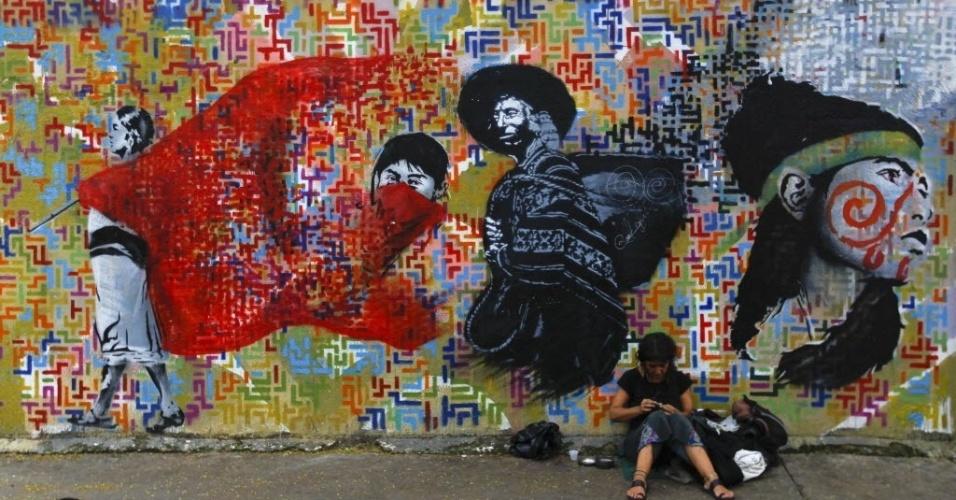 """Mulher se senta ao lado de parede com grafite inspirado em foto """"Woman with flag"""" de 1928, de autoria da fotógrafa italiana Tina Modotti"""
