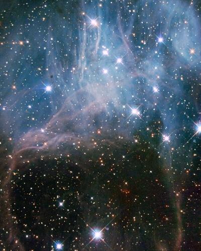 A imagem obtida pelo telescópio Hubble da Nasa (agência espacial americana) mostra estrelas brilhantes e uma névoa no céu em uma das regiões de maior concentração de estrelas jovens na Grande Nuvem de Magalhães, galáxia vizinha da Via Láctea
