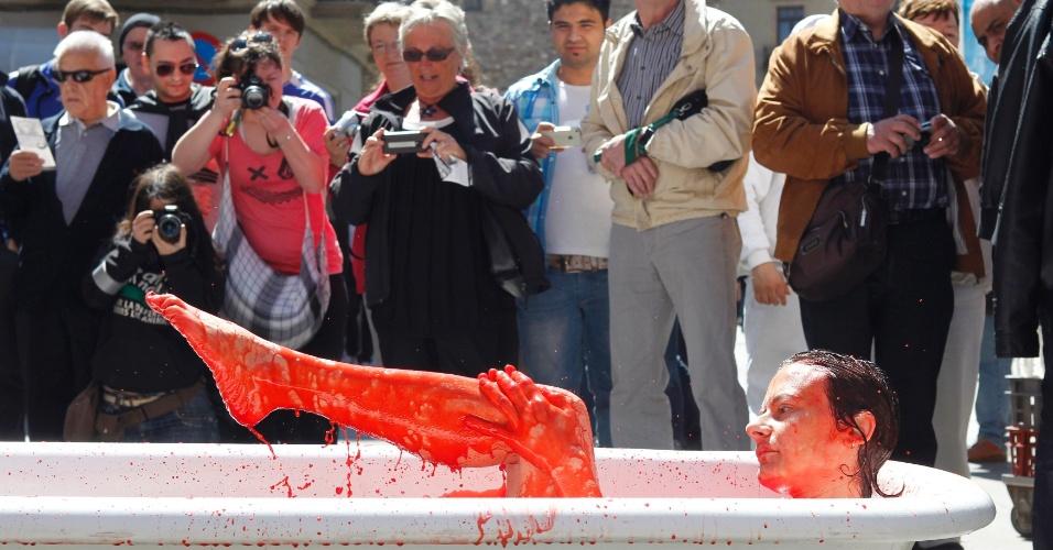Curiosos observam ativista em protesto no centro de Barcelona, na Espanha, contra o uso de animais em pesquisas para o desenvolvimento de novos produtos cosméticos e de higiene pessoal