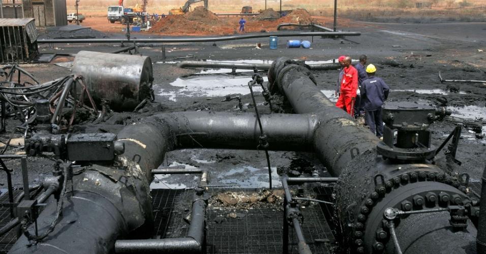 Engenheiros caminham em área destruída de refinaria na região de Heglig, área disputada com o Sudão do Sul