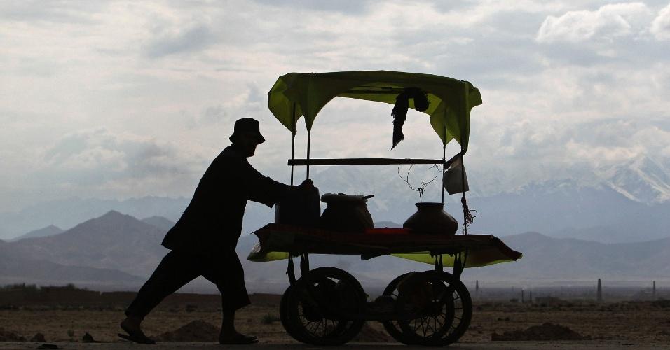 Homem empurra seu carrinho ao longo de uma estrada nos arredores de Cabul