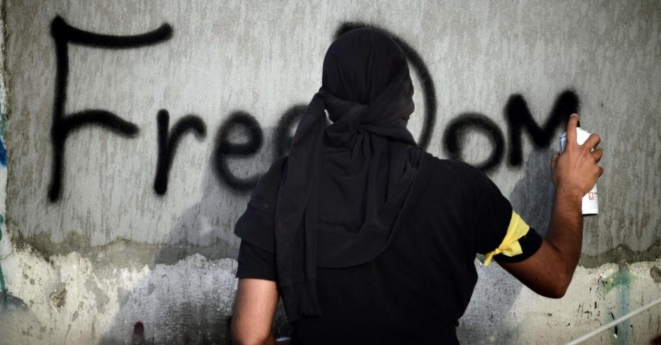 """Jovem picha a palavra """"liberdade"""" em parede durante ato de solidariedade ao ativista Salah Abbas Habib, encontrado morto após confronto com a polícia no vilarejo de Shakhoura, ao norte da capital Manama"""